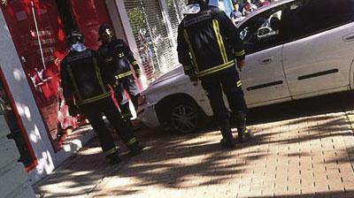 Un vehículo cruza la rotonda y se empotra contra un escaparate