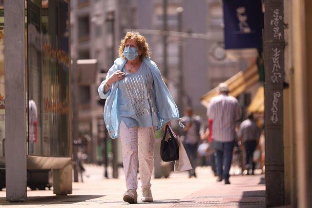 Una mujer pasea con mascarilla. - Iñaki Berasaluce - Europa Press