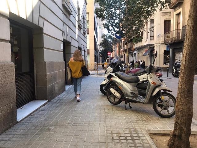 Motos aparcadas en la acera en una calle del barrio de la Vila de Gràcia.