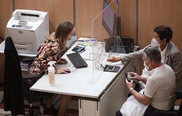 Una trabajadora de una oficina de la Agencia Tributaria atiende a dos personas. - Eduardo Parra - Europa Press - Archivo