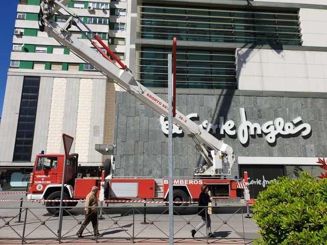 Los bomberos retiran un panel de cristal dañado en El Corte Inglés como medida de prevención