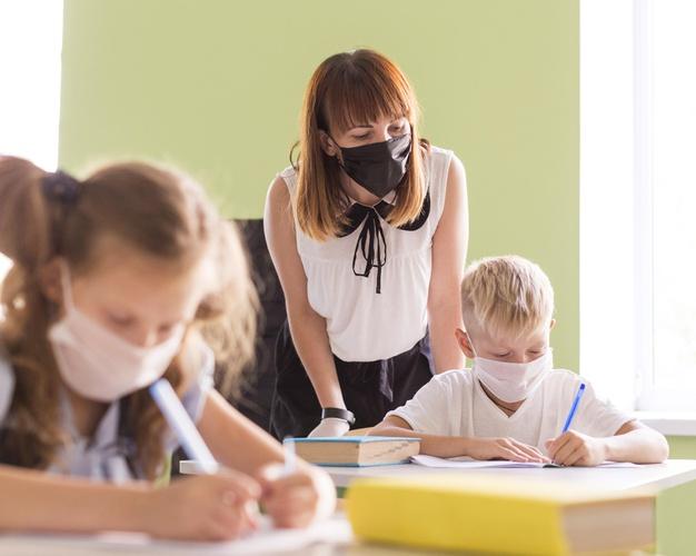 Maestros y niños protegiéndose con mascarillas en clase | Foto: Freepik