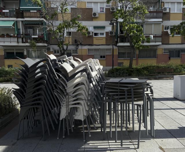 Sillas y mesas apiladas en una terraza cerrada | Archivo